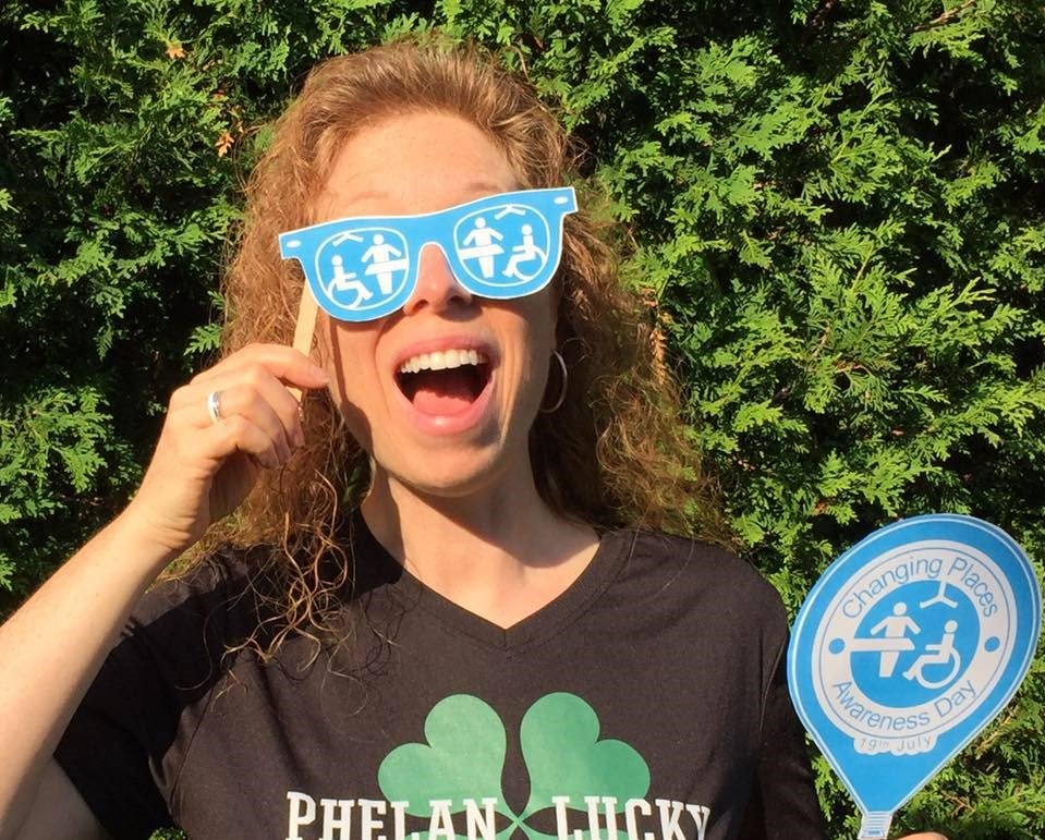 Stephanie Lecler with a big smile holding paper eye glasses with Changing Places logo on them